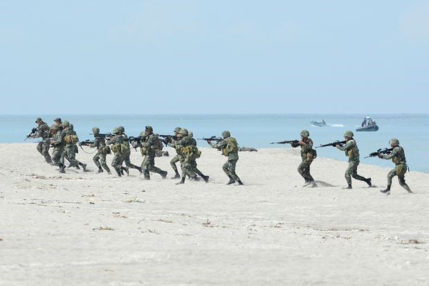 Philippine and US marines take their positions during a beach assault exercise facing the South China sea in San Antonio town, Zambales province in May 2014.
