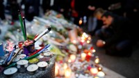 People light candles outside the offices of the French satirical newspaper Charlie Hebdo in Paris on January 10, 2015
