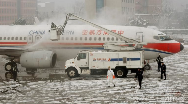 File photo of airport workers removing snow and ice from a China Eastern plane, taken at Shanghai's Hongqiao airport.