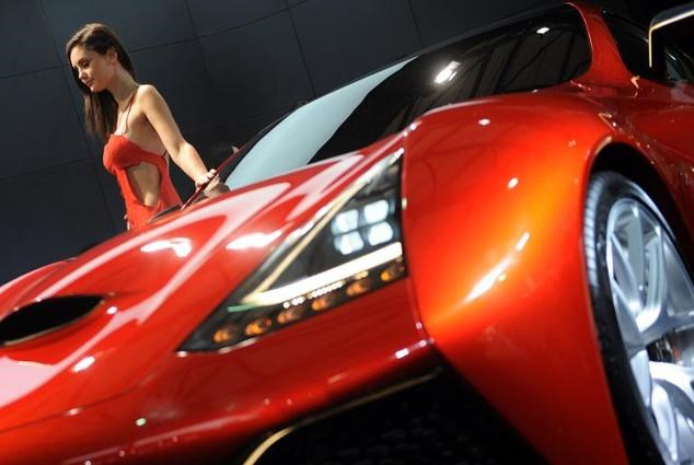 A model posing next to an Icona design concept car on media day at the Shanghai auto show, April 20, 2013 .