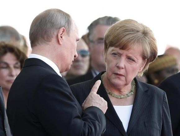 Russian President Vladimir Putin talks with German Chancellor Angela Merkel as they attend the International 70th D-Day Commemoration Ceremony in Ouistreham June 6, 2014.