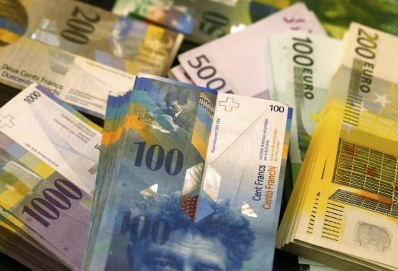 A file photo shows Swiss Franc and Euro banknotes of several values lying on a table in a Swiss bank in Bern November 25, 2014.
