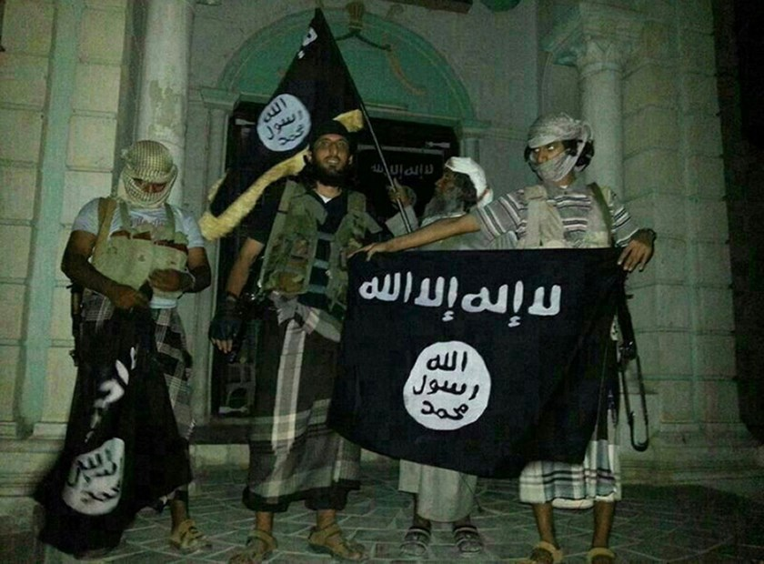 A picture taken with a mobile phone early on May 24, 2014 shows militants posing with Islamic State flags in front of a museum in Seiyun, Yemen.
