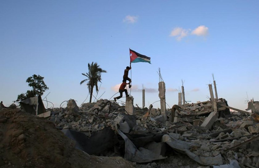 Children in Khan Yunis' Khuzaa neighbourhood in the southern Gaza Strip place a Palestinian flag on October 1, 2014, in the rubble of a building destroyed during the Israeli army's summer offensive on the Gaza Strip