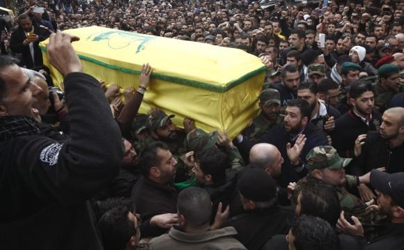 Hezbollah members and supporters carry the coffin of Jihad Moughniyah during his funeral in Beirut's suburbs January 19, 2015.