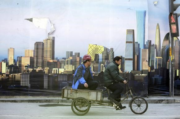A worker rides past a poster showing Beijing's central business district outside a construction site in Beijing, December 29, 2014.