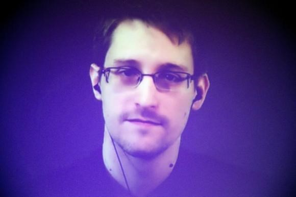 Former U.S. National Security Agency contractor Edward Snowden, who is in Moscow, is seen on a giant screen during a live video conference for an interview as part of Amnesty International's annual Write for Rights campaign at the Gaite Lyrique in Paris D