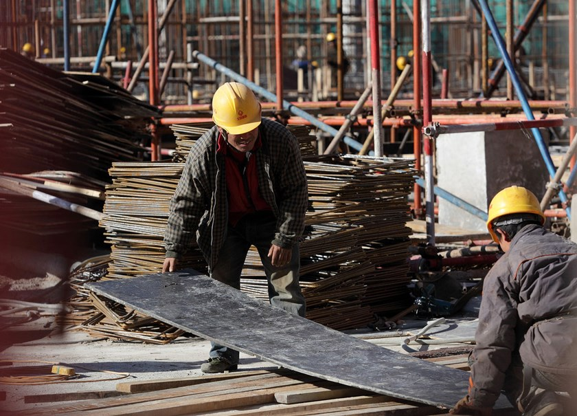 Workers labor at a construction site for a residential building on the outskirts of Beijing, China.