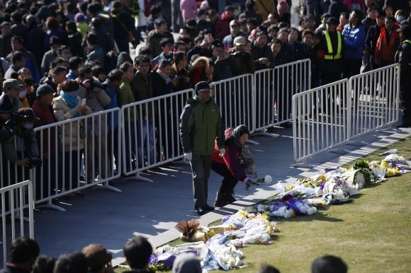 People lay down flowers during a memorial ceremony in memory of people who were killed in a stampede incident during a New Year's celebration on the Bund, in Shanghai January 1, 2015.