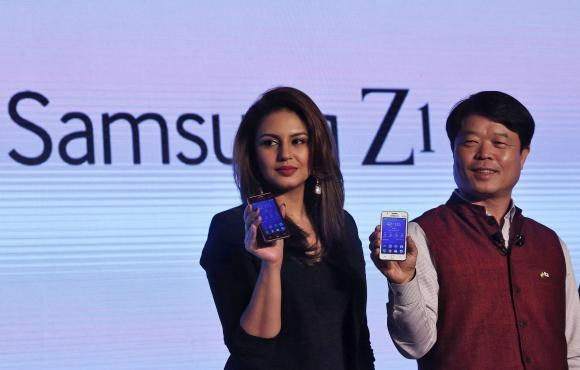 Hyun Chil Hong (R), president and chief executive of Samsung India Electronics, and Bollywood actress Huma Qureshi hold the Samsung's new Z1 smartphones at its launch in New Delhi January 14, 2015.