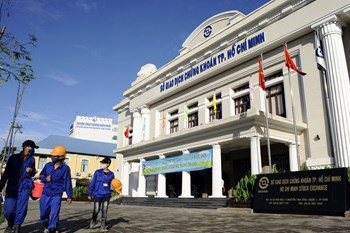 Workers walk past the Ho Chi Minh Stock Exchange building in Ho Chi Minh City.