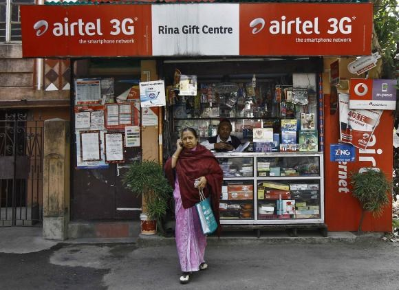 A woman speaks on her mobile phone after recharging it at a local stationary cum prepaid mobile recharge shop in Kolkata January 19, 2015.