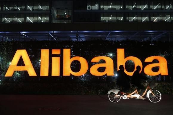 People ride a double bicycle past a logo of The Alibaba Group at the company's headquarters on the outskirts of Hangzhou, Zhejiang province in this file photo taken November 10, 2014.