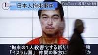 A man walks past screens displaying a television news programme showing an image of Kenji Goto, one of two Japanese citizens taken captive by Islamic State militants, on a street in Tokyo January 25, 2015.
