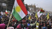 Kurdish civilians gather in the Syrian Kurdish city of Qamishli as they wave Kurdish flags in celebration after it was reported that Kurdish forces took control of the Syrian town of Kobani January 27, 2015.