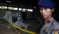 A police officer stands near part of the fuselage of crashed AirAsia Flight QZ8501 inside a storage facility at Kumai port in Pangkalan Bun, January 19, 2015.