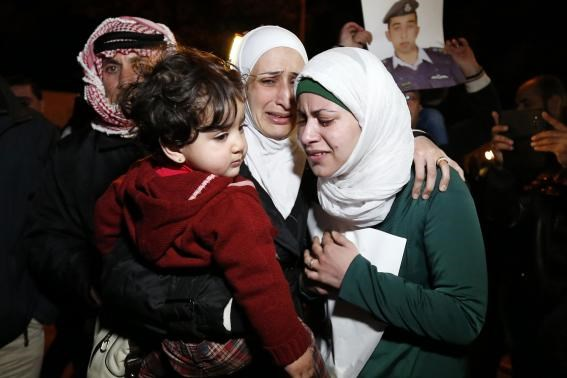 Anwar Tarawneh (R), the wife of Islamic State captive Jordanian pilot Lieutenant Muath al-Kasaesbeh, and his sister (C) weep after listening to a statement released by Islamic State in front of the Royal Palace in Amman January 28, 2015.