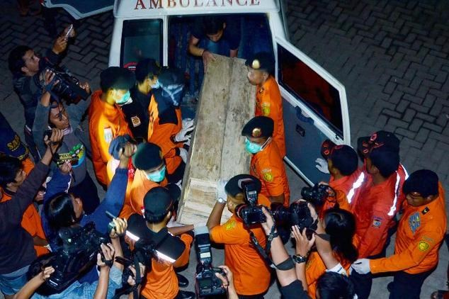 Photo taken on February 1, 2015 shows rescue personnel unloading a casket containing the recovered remains of a victim of the ill-fated AirAsia flight QZ8501 upon its arrival at Makassar hospital, Sulawesi.