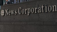 A passer-by stands in front of the News Corporation building in New York June 28, 2012.