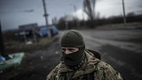 A Ukrainian soldier stands watch on a road between Debaltseve and the Ukrainian-controlled town of Artemivsk, in the Donetsk region, on February 2, 2015