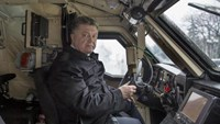 Ukraine's President Petro Poroshenko sits in the driver's seat of an armoured vehicle in Kiev, January 30, 2015, in this handout courtesy of the Ukrainian Presidential Press Service.