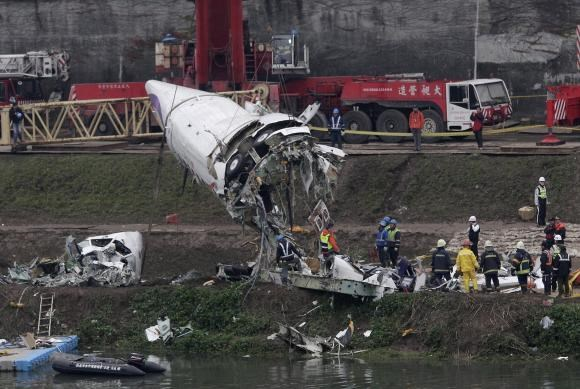 Emergency teams remove pieces of wreckage at the site of the crashed TransAsia Airways plane Flight GE235 in New Taipei City February 5, 2015.