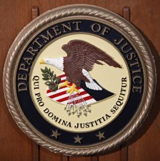 The Department of Justice logo is seen on the podium during a news conference in New York January 23, 2013.