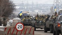 Ukrainian government troops sit in the back of pick-up trucks as they pass a checkpoint near the town of Mariupol, Ukraine, Tuesday, Feb. 10, 2015.