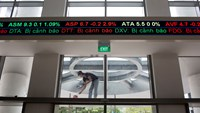 An electronic stock ticker displays share prices as a laborer paints outside the Ho Chi Minh Stock Exchange (HOSE) in Ho Chi Minh City. While Vietnam's stock market has outperformed, volumes are still dwarfed larger peers.