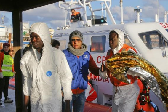 Migrants who survived a shipwreck are escorted as they arrive at the Lampedusa harbour February 11, 2015.