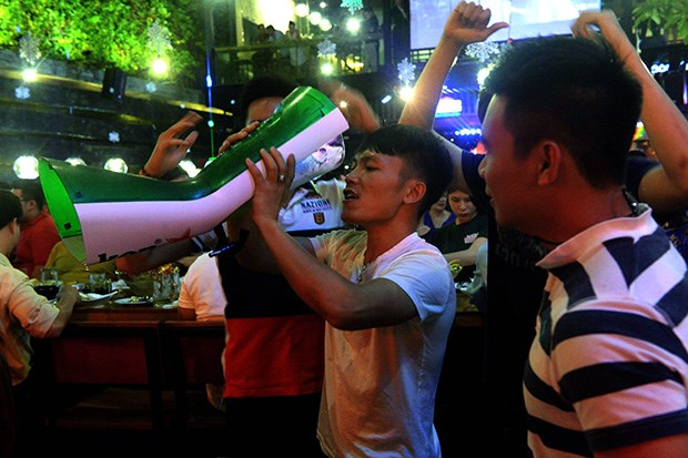 A man drinks beer from a tower as his friends look on at a local open-air beer bar in downtown Ho Chi Minh City.