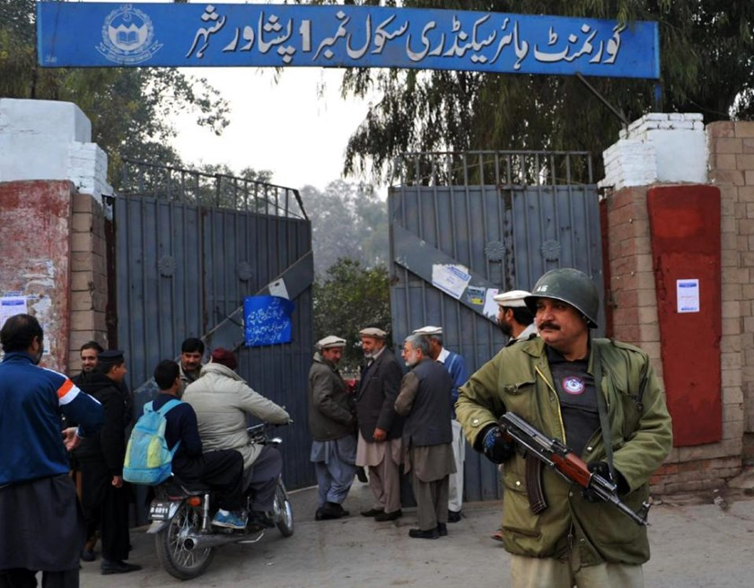 A policeman stands guard outside a government school in Peshawar after schools in the city reopened on January 12, 2015 following a Taliban attack