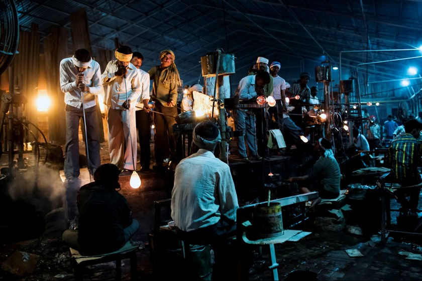 Glass blowers work molten glass in the blowing area of a Pooja Group of Glass Industries factory in Ferozabad, Uttar Pradesh, India, on Feb. 21, 2015.