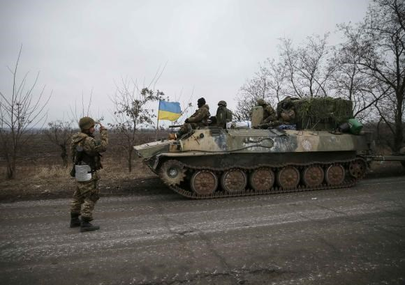 A convoy of Ukrainian armed forces including armoured personnel carriers, military vehicles and cannons prepare to move as they pull back from the Debaltseve region, in Paraskoviyvka, eastern Ukraine, February 26, 2015.