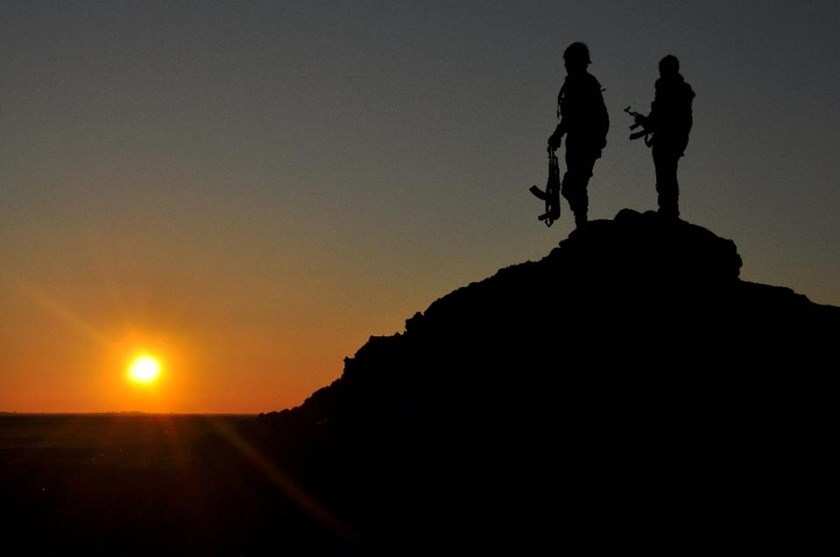 People's Protection Units (YPG) fighters stand on a hill at sunset on February 26, 2015, after they retook parts of the town of Tal Hamis, southeast of the city of Qameshli, after six days of clashes with Islamic State (IS) group jihadists