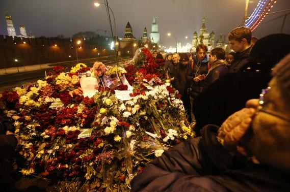 People gather at the site where Boris Nemtsov was recently murdered, with St. Basil's Cathedral and the Kremlin walls seen in the background, in central Moscow, February 28, 2015.