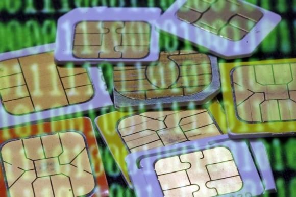 SIM cards are reflected on a monitor showing binary digits in this photo illustration taken in Sarajevo February 23, 2015.