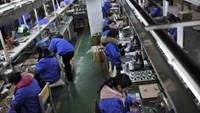 Employees assemble electronic components along a production line at a factory in Hefei, Anhui province, January 18, 2015.