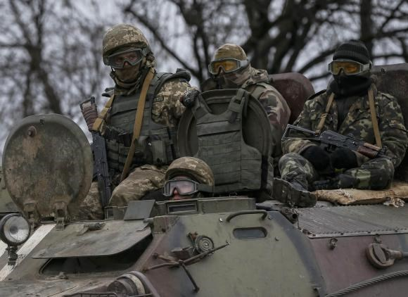 Members of the Ukrainian armed forces ride on an armoured personnel carrier near Artemivsk, eastern Ukraine, February 28, 2015.