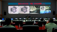 Chinese technicians at the Jiuquan Space Centre monitor the Shenzhou-9 spacecraft as it prepares to link with the Tiangong-1 module just over a week into a manned space mission which includes China's first female astronaut, following an automatic docking,