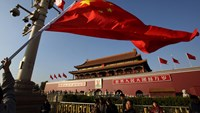 A worker lowers a Chinese national flag in front of Tiananmen Gate in Beijing.