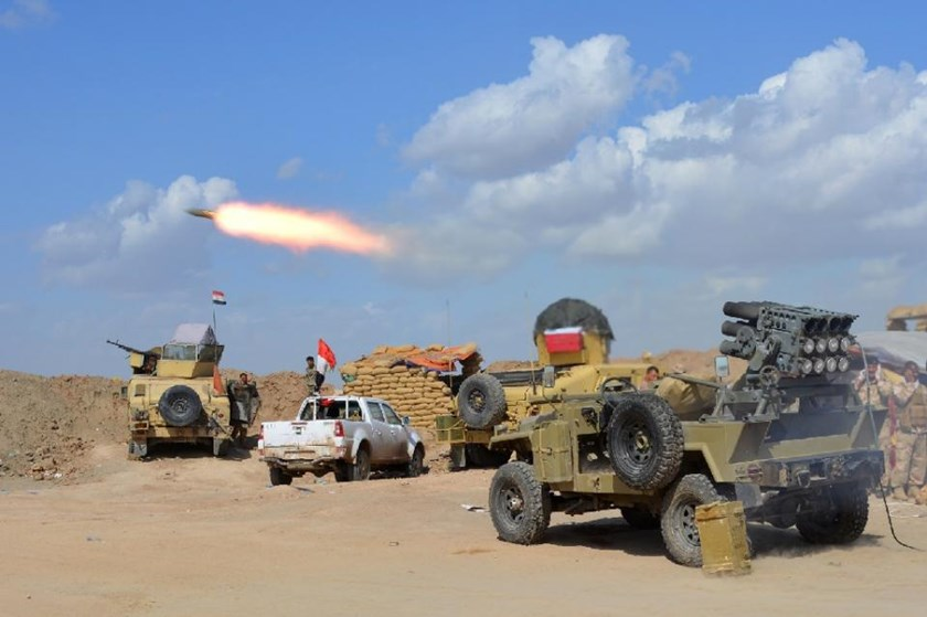 Iraqi government forces and allied militias fire weaponry from a position in the northern part of Diyala province, bordering Salaheddin province, as they take part in an assault to retake the city of Tikrit from IS jihadists, on March 2, 2015