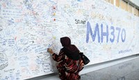 A woman writes a message on a banner for missing Malaysian Airline System Bhd. (MAS) flight MH370 at Kuala Lumpur International Airport (KLIA) in Sepang, Malaysia, on March 14, 2014.