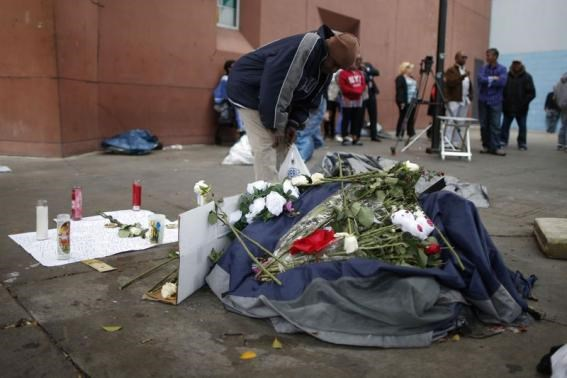 A man views a memorial for a man killed by police on skid row in Los Angeles, California, March 2, 2015.
