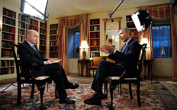 President Barack Obama (R) speaks during an interview with White House Correspondent Jeff Mason in the Library of the White House