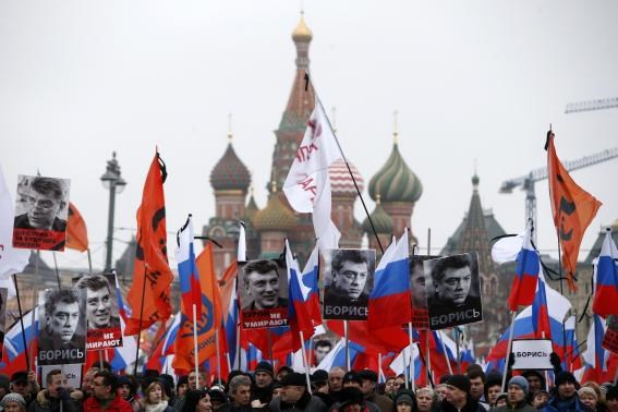 People hold flags and posters during a march to commemorate Kremlin critic Boris Nemtsov, who was shot dead on Friday night, near St. Basil's Cathedral in central Moscow March 1, 2015.