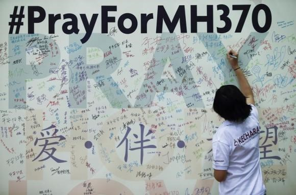 A woman writes a message on a board for family members of passengers onboard the missing Malaysia Airlines Flight MH370 at the Malaysian Chinese Association (MCA) headquarters in Kuala Lumpur April 6, 2014.