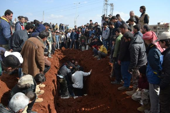 People bury the bodies of eight Hazzm brigade fighters, who were killed during clashes with al Qaeda's official Syria wing Nusra Front fighters in Reef al-Mohandeseen al-Thani and the Mashtal area, in Al-atarib Aleppo countryside February 28, 2015.
