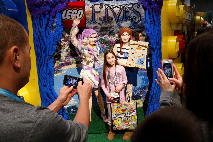 An attendee has her picture taken with life-size models to introduce the LEGO Elves fantasy theme at the American International Toy Fair.