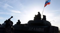 A Russian flag flies on a howitzer as a military convoy withdraws from the eastern Ukrainian city of Starobeshevo, on February 25, 2015